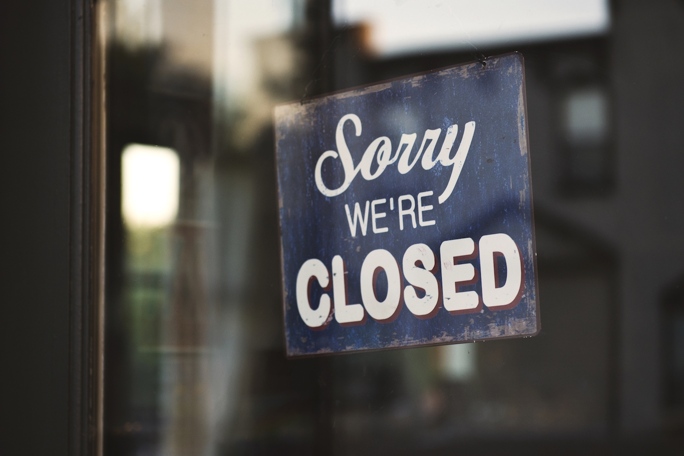 closeup shot blue white sorry we are closed wooden signage glass