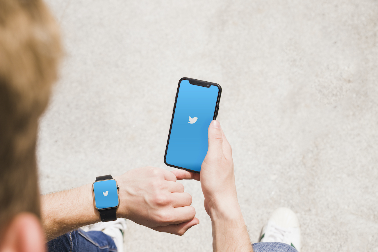 close up man with smartwatch cellphone showing twitter app