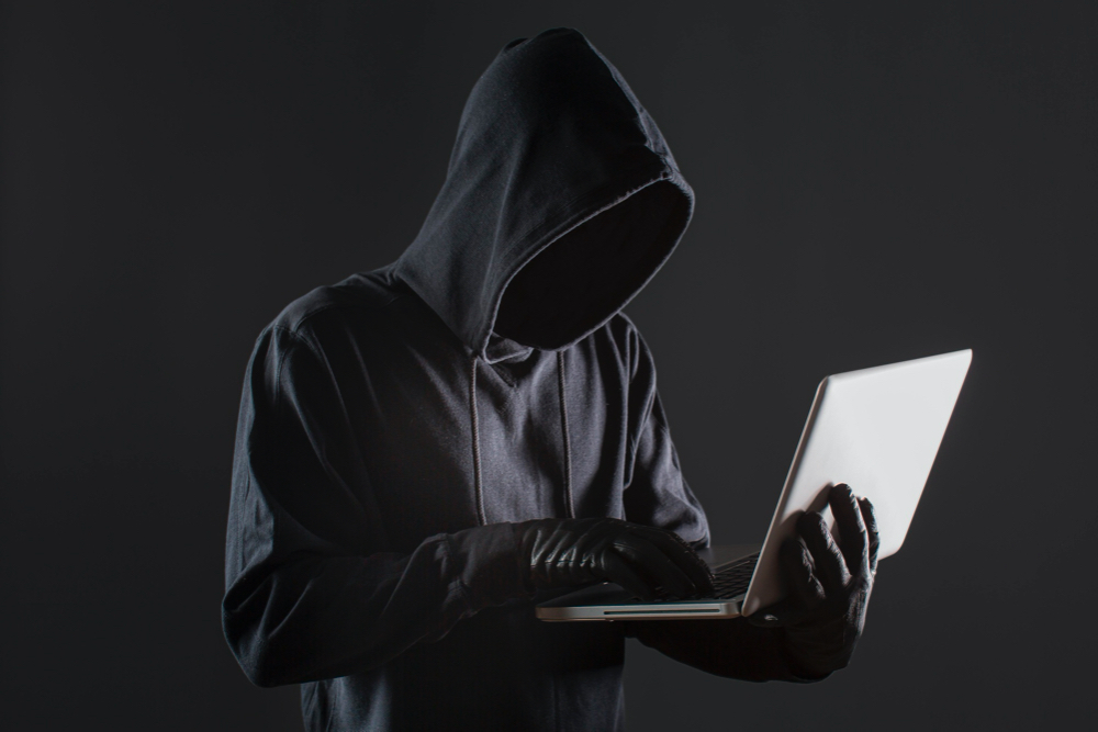 side view male hacker with gloves laptop